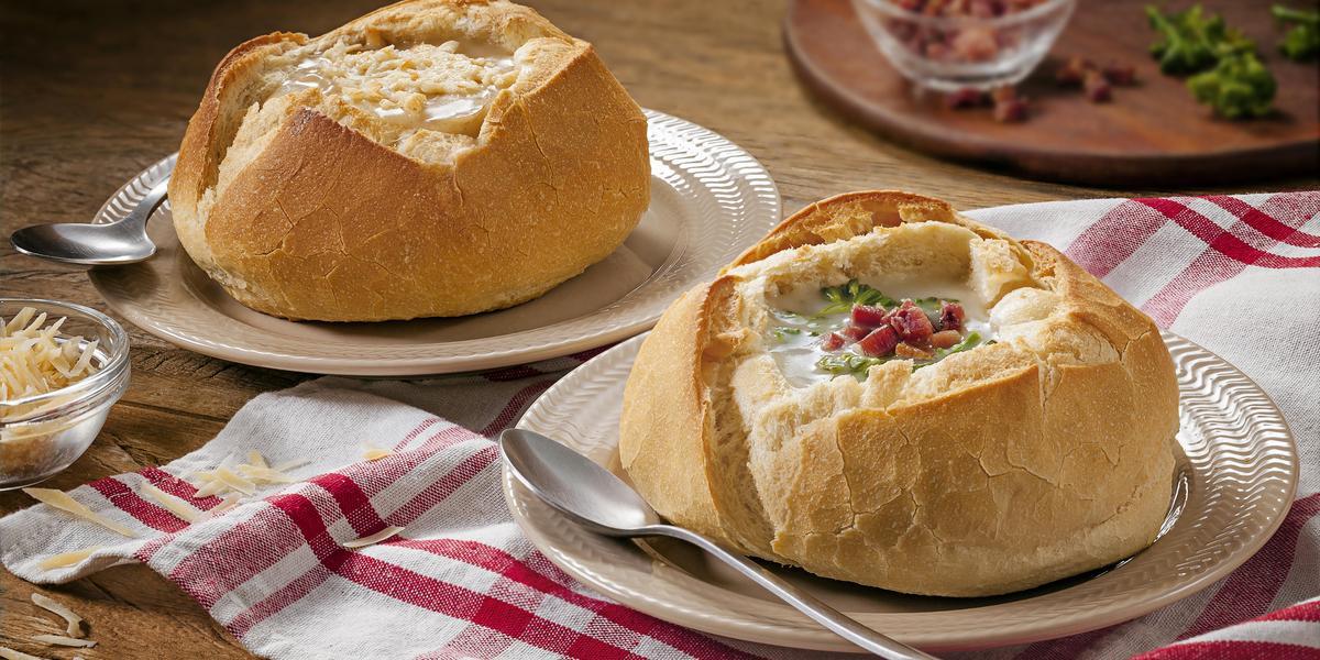 Fotografia em tons de vermelho em uma bancada de madeira com um pano xadrez vermelho, dois pratos rasos bege com duas sopas de creme de queijo com brócolis e bacon dentro do pão italiano.