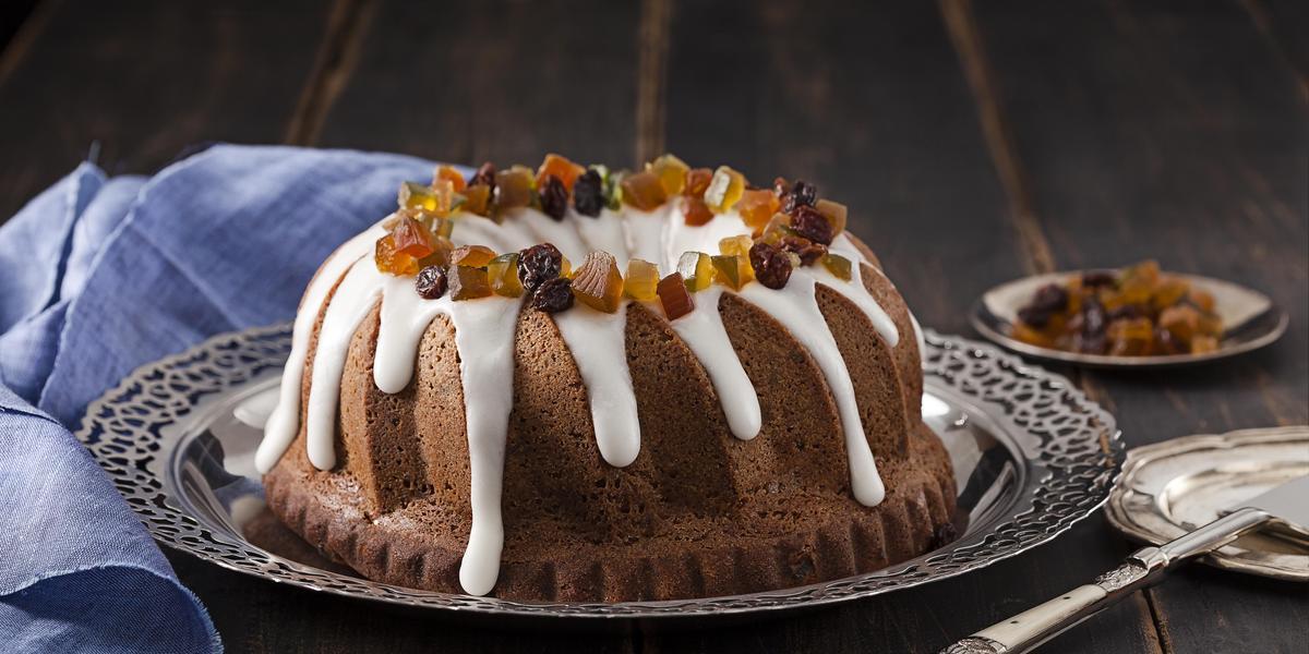 Fotografia em tons de marrom em uma bancada de madeira escura com um pano azul ao lado e um prato fundo de prata ao centro com o bolo dos reis dentro. Ao fundo, um prato pequeno com algumas frutas cristalizadas.