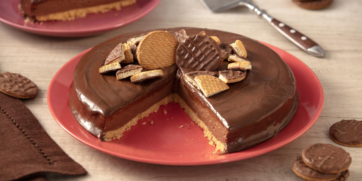 Foto de uma bancada clara. Sobre ela há um guardanapo de pano marrom, alguns Biscoitos Calipsos cobertos com chocolate espalhados e, ao centro, um prato vermelho com a receita pronta, sem uma fatia, mostrando o interior. Há um prato ao fundo com a fatia.