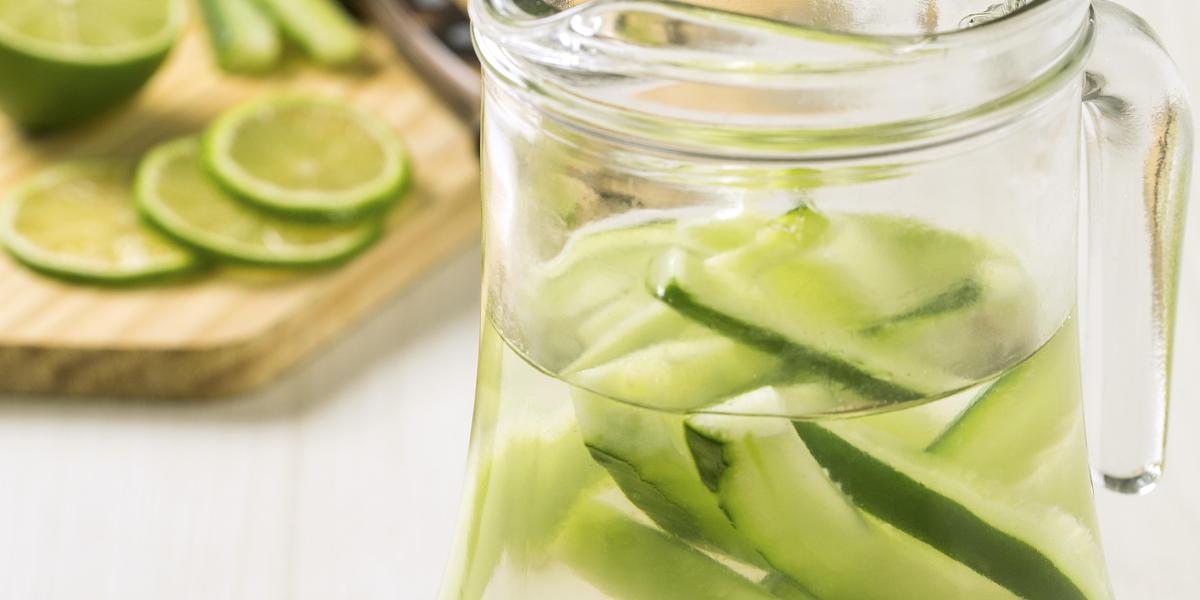 Fotografia em tons de branco e verde de uma bancada verde com uma jarra de vidro, dentro dela a água aromatizada. Ao fundo uma tábua de madeira com limões e uma faca.