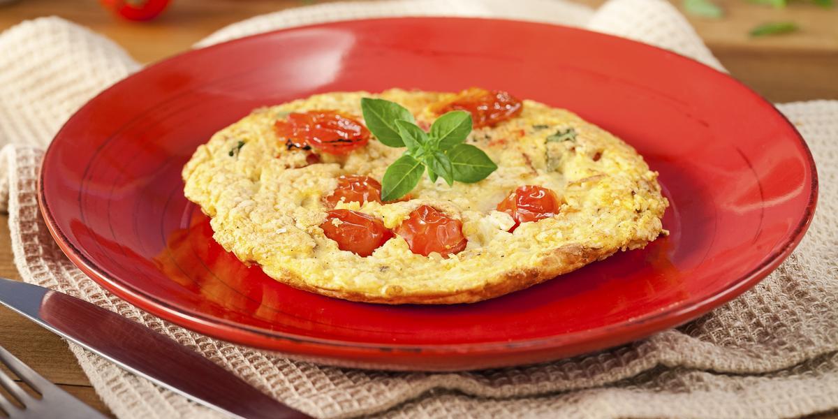 Fotografia em tons de vermelho em uma bancada de madeira, um pano bege, um prato vermelho redondo com a omelete com tomates-cereja em cima dele. Ao fundo, tomatinhos para decorar e ao lado, garfo e faca.