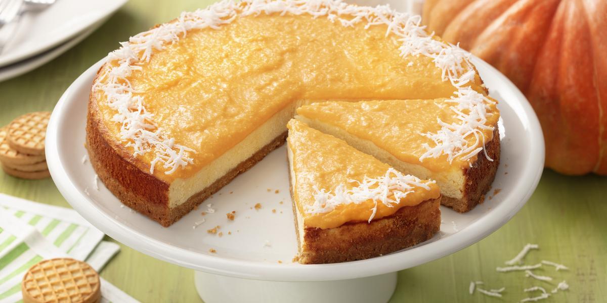 Fotografia em tons de verde e laranja de uma bancada de madeira verde com um paninho listrado verde e branco com biscoitos  e uma bailarina branca com o cheesecake de abóbora. Ao fundo uma abóbora, um coco e um prato quadrado branco.