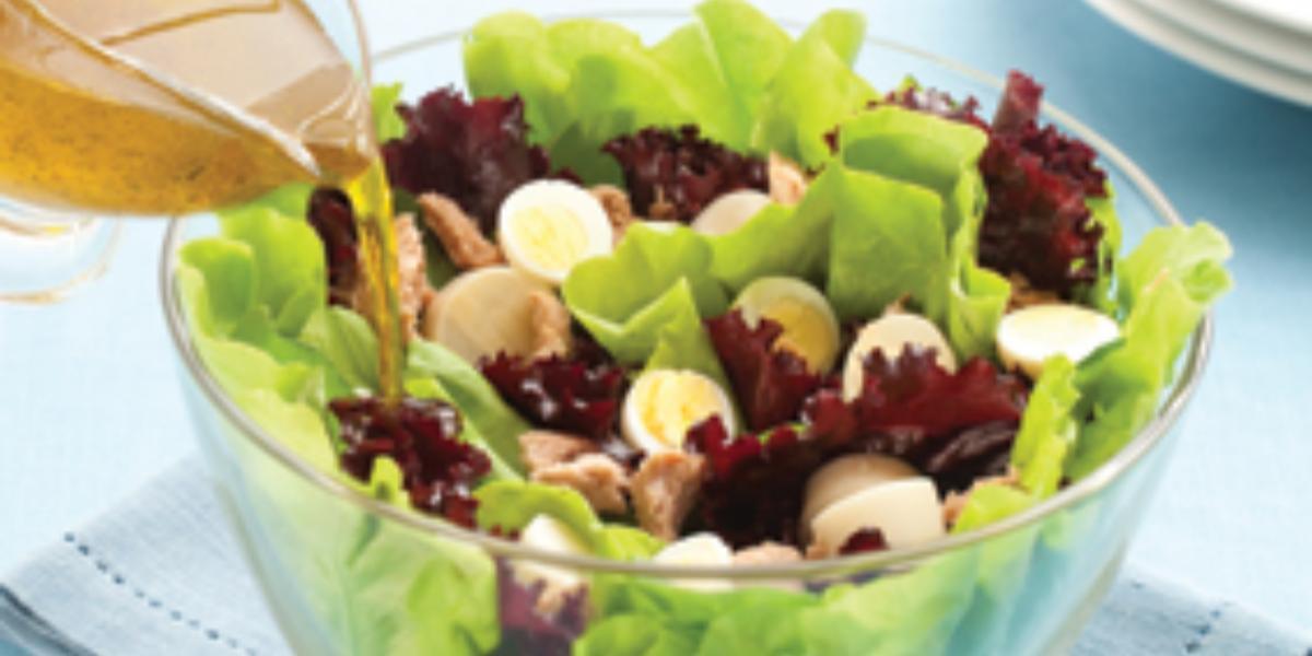 Fotografia em tons de azul e verde, com saladeira transparente sobre guardanapo azul contendo folhas verdes e roxas, palmito e ovos de codorna, regada com molho, sobre toalha azul.