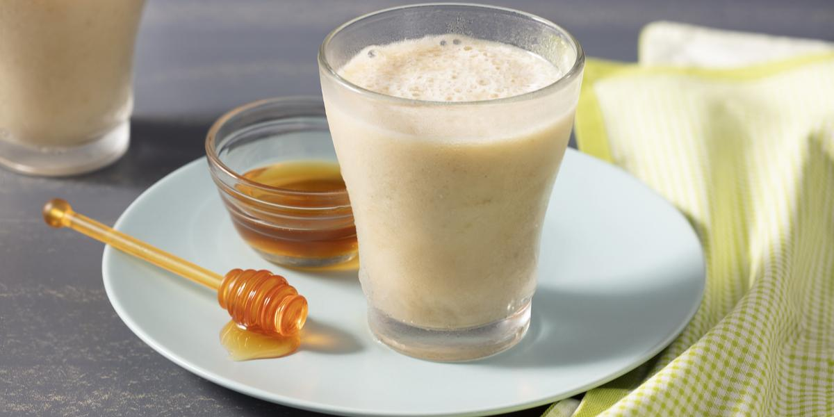 Fotografia em tons de amarelo com fundo cinza com prato branco redondo azul claro, potinho e pegador de mel, um copo de vidro com a bebida e um pano quadriculado verde e branco.