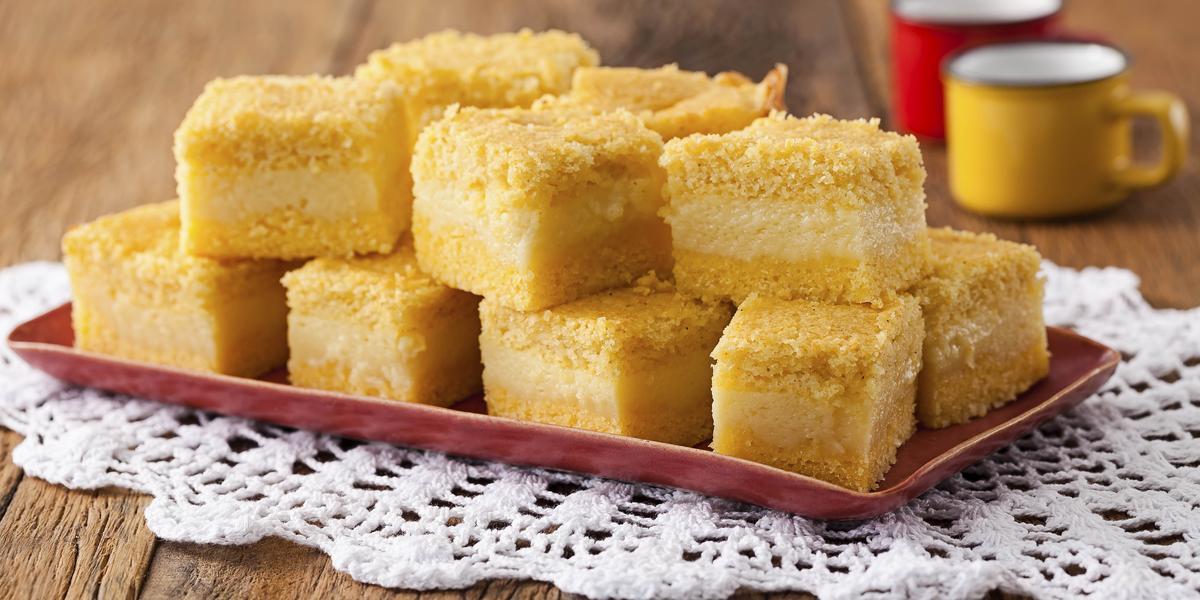 8 pedaços quadrados de bolo amarelo com uma lista branca no meio, dispostos em um prato vermelho que está em cima de uma toalha branca