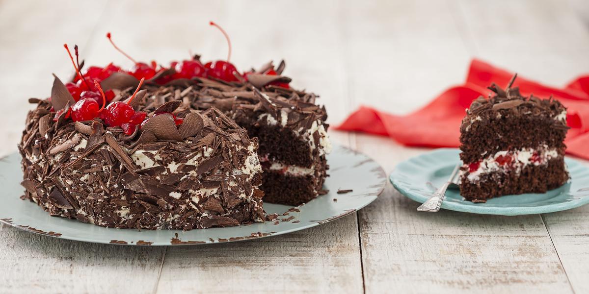 Fotografia em tons de marrom e branco de bancada de madeira, com prato azul com o bolo confeitado com raspas de chocolate e cerejas com uma fatia retirada. Ao lado prato azul com a fatia mostrando o recheio, talher prateado e ao fundo paninho vermelho.