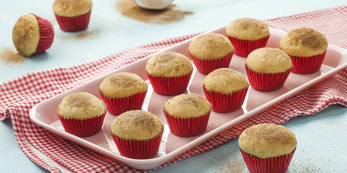 Fotografia em tons de azul claro e vermelho com prato retangular rosa claro com o bolinho de chuva assado dentro de forminhas vermelhas. Abaixo do prato está um tecido quadriculado vermelho e branco.