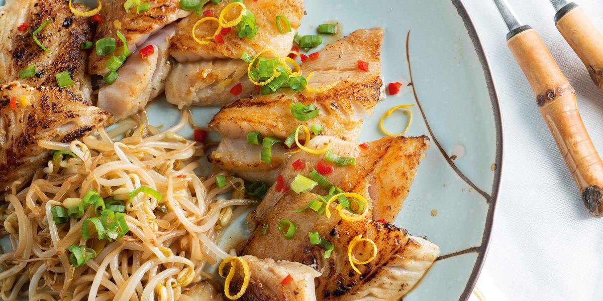 Fotografia em tons de azul, branco e dourado, com bancada azul vista de cima, tendo ao centro prato azul com borda marrom contendo peixe frito e broto de feijão, ao lado guardanapo branco e dois garfos com cabo imitando bambu.