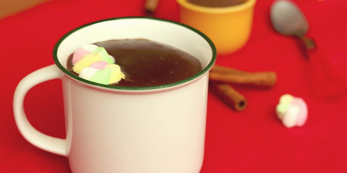 Fotografia em tons de branco e vermelho, ao centro uma xícara branca com chocolate quente e marshmallows, sobre toalha vermelha. Atrás um potinho com achocolatado e uma colher, com paus de canela e marshmallows espalhados ao redor.