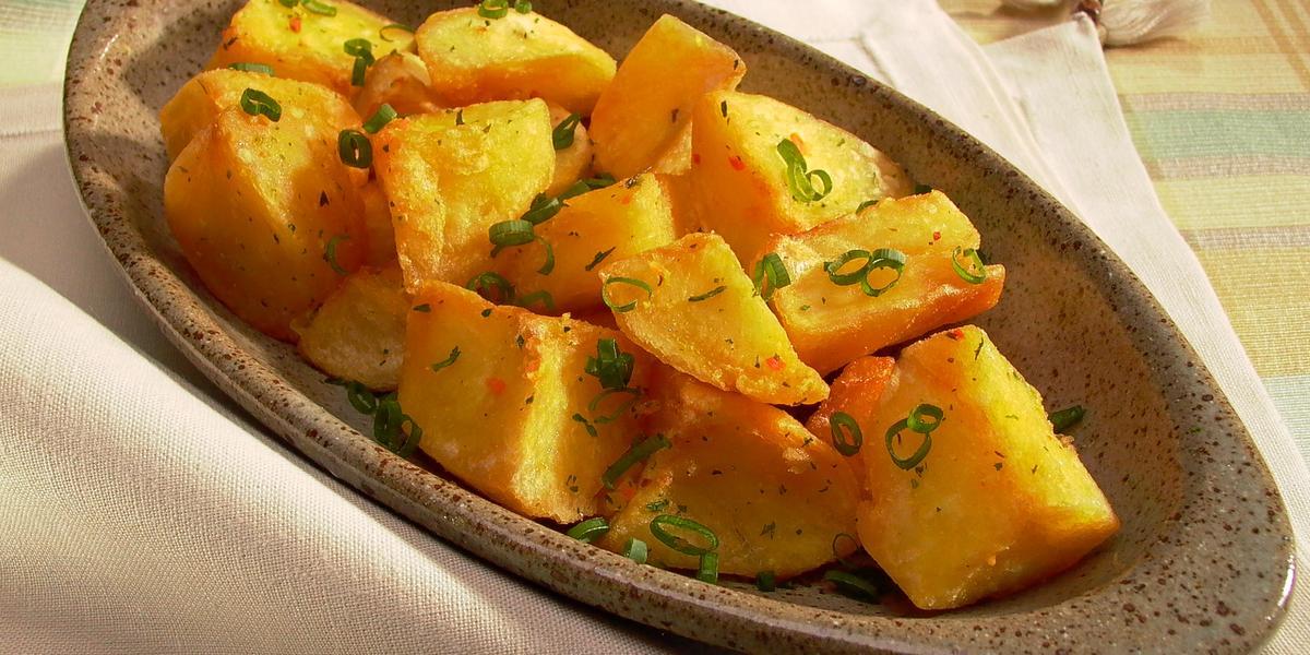 Fotografia em tons de amarelo em uma mesa com uma toalha quadriculada em amarelo, laranja e verde e um recipiente oval fundo com batatas cozidas e cebolinha-verde dentro dele.