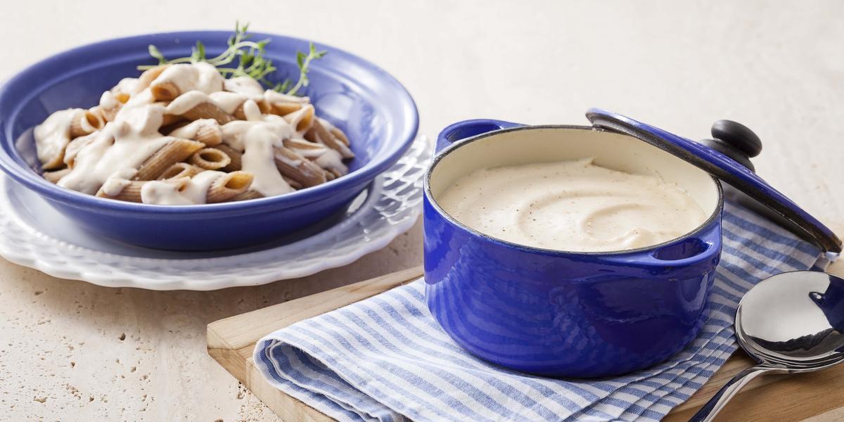 Foto de uma panela azul com molho branco dentro, em cima de uma tábua de madeira e um pano azul com branco. Do lado esquerdo, um prato de macarrão com molho branco em cima