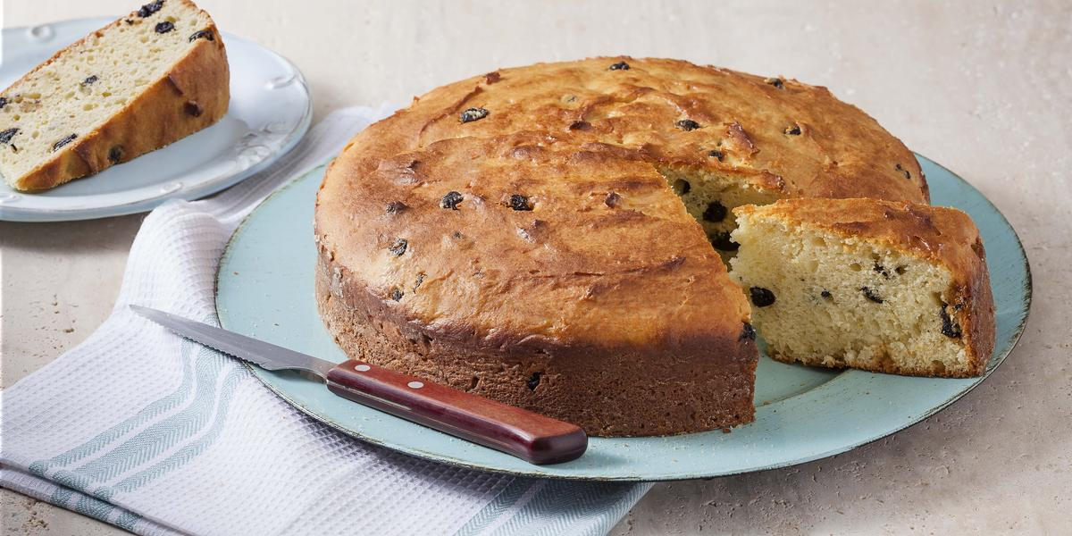 fotografia em tons de cinza, azul e bege de uma bancada cinza vista de frente. Contém um pano azul, um prato azul redondo com um bolo com a fatia retirada. Ao fundo um prato redondo azul com uma fatia de bolo.