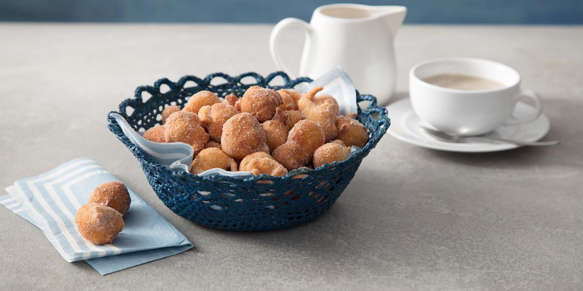 Foto com uma cesta azul repleta de bolinhos de chuva dentro, ao lado esquerdo da cesta há dois bolinhos soltos e no fundo há uma xícara branca e uma jarra branca