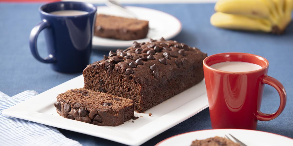 Foto de uma bancada clara, sobre a qual há um prato retangular no centro com o bolo pronto. dois pratos redondos brancos, um de cada lado, com fatias do bolo e duas canecas, uma azul e uma vermelha, com leite e Nescau misturados dentro