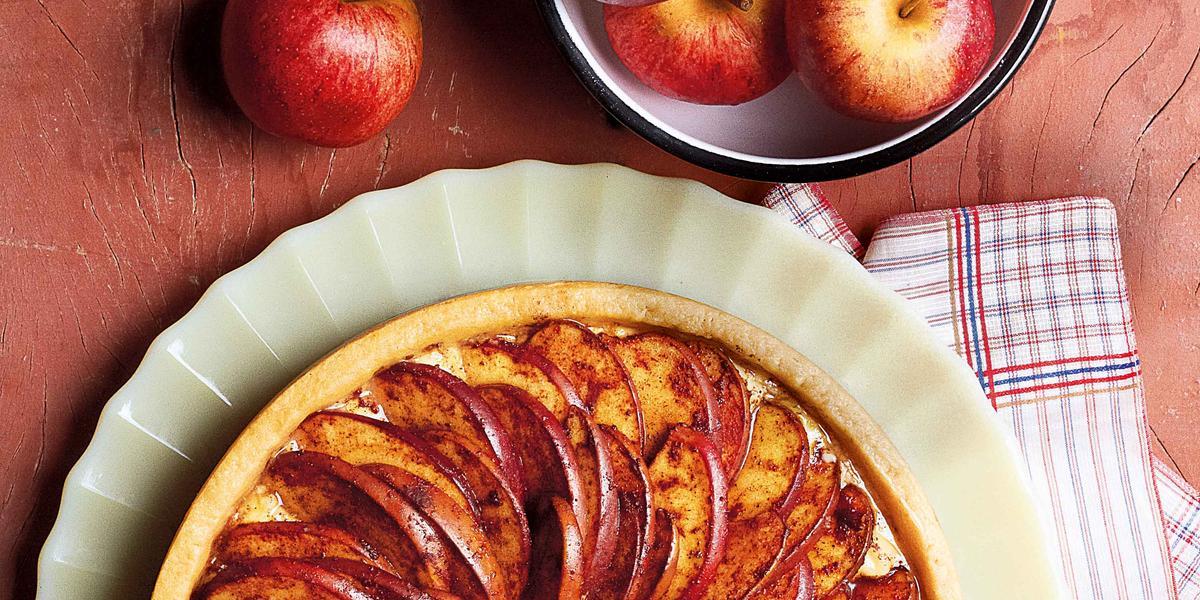 Foto tirada de cima de uma torta redonda de maça em cima de um prato branco. A torta é decorada por várias maças cortadas