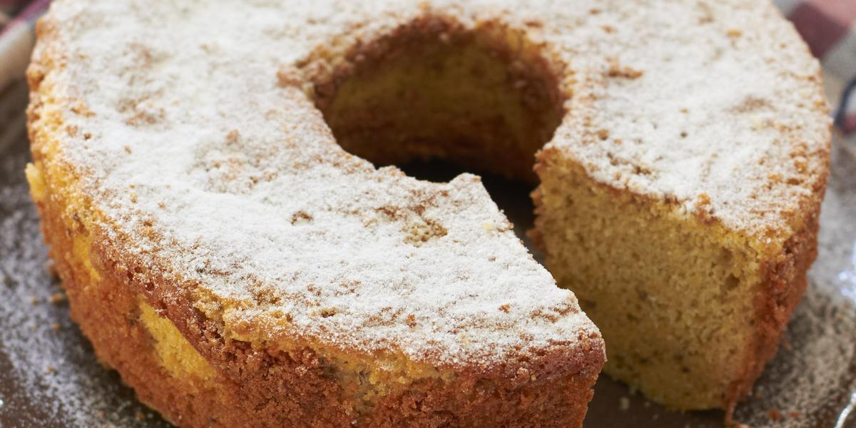 em uma mesa de madeira contém um pano xadrez nos tons vinho e cinza e por cima do pano o bolo de fubá coberto com açúcar de confeiteiro.