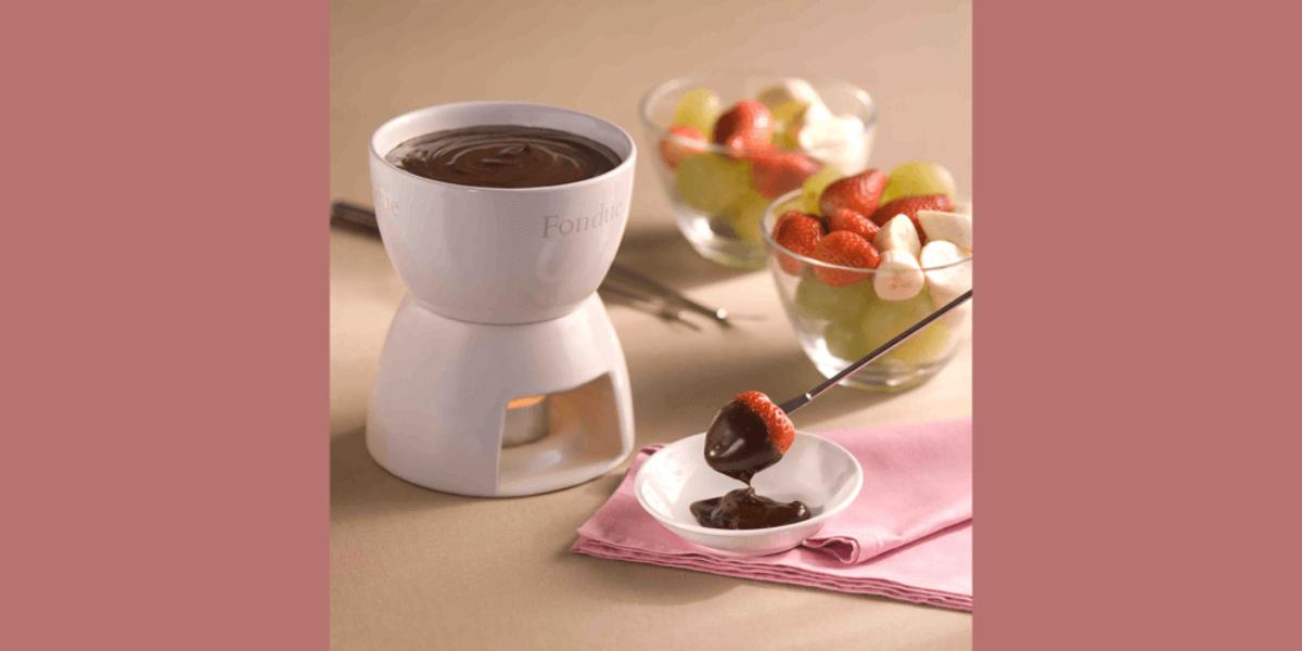 Fotografia de uma panela de fondue de cerâmica branca e aquecida com uma vela abaixo. Ao lado frutas frescas como morango, uva e banana em dois recipientes de vidro e um garfo próprio para fondue com uma morango coberto de chocolate.