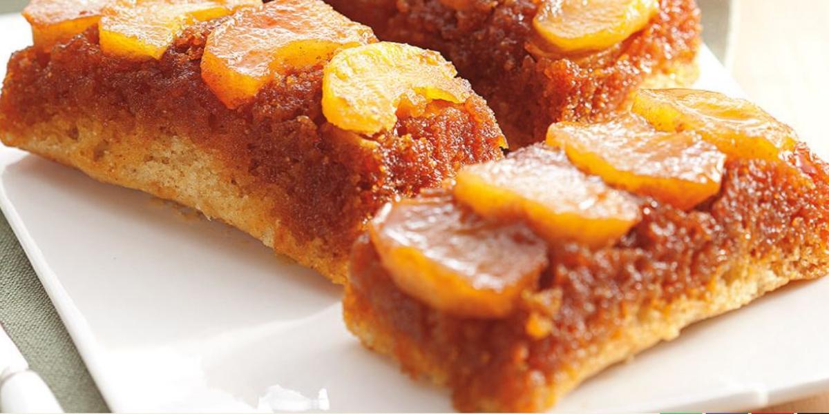 Fotografia em tons de marrom em uma bancada de madeira com um prato branco quadrado ao centro e três fatias de bolo integral de maçã e canela. Ao fundo, um bule branco e pratos rasos brancos empilhados.