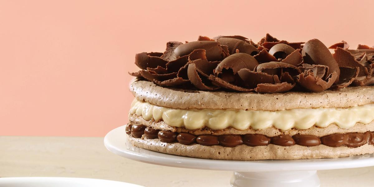 Fotografia em tons de rosa em uma mesa de madeira branca com um pano de prato vermelho, uma parede de fundo rosa, um suporte para bolo branco com a torta de macaron de chocolate e creme de avelã.