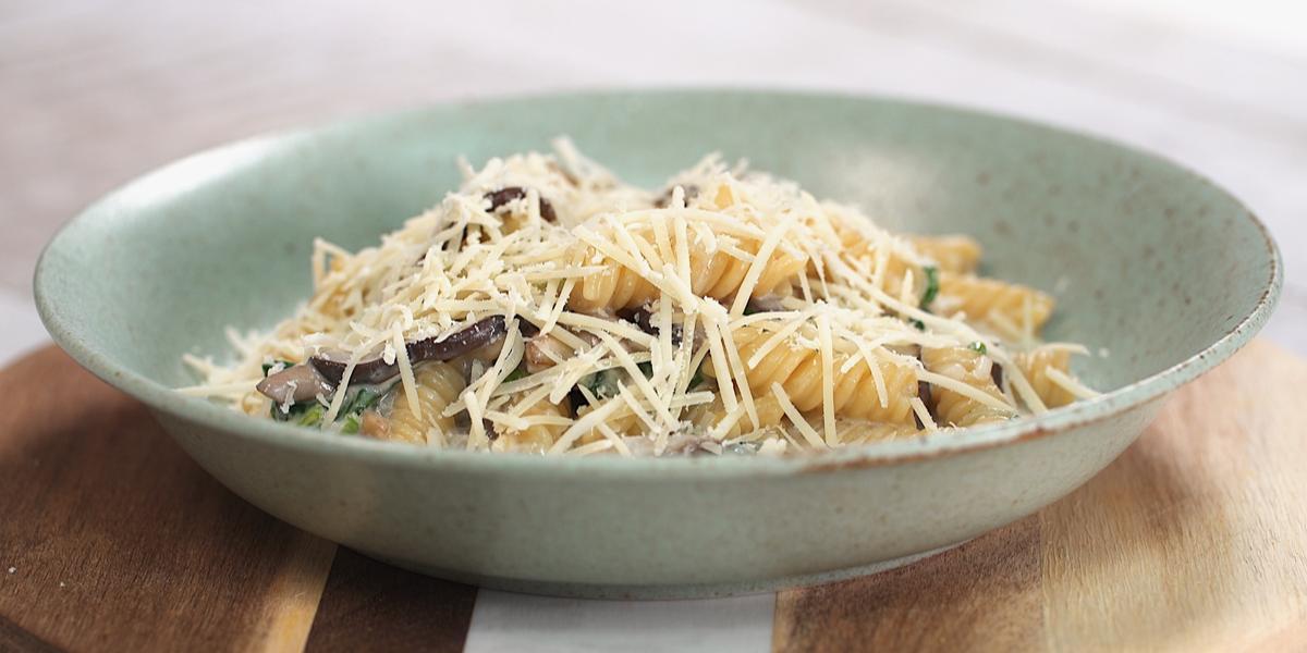 Fotografia em tons de marrom e verde de uma bancada de madeira, sobre ela um prato redondo verde com o macarrão.