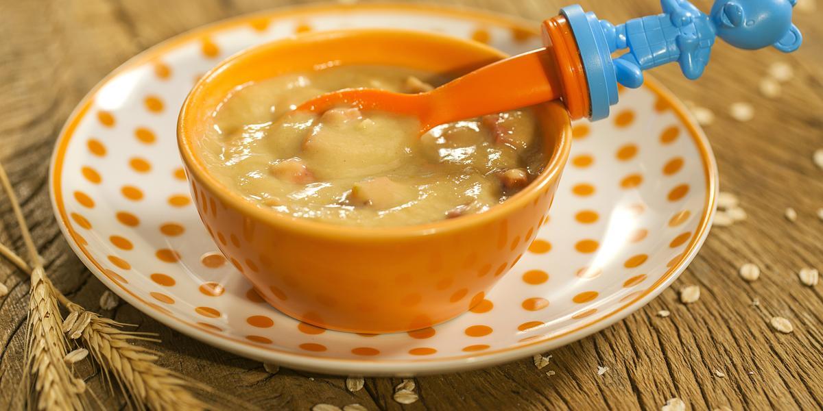 Fotografia em tons de marrom e laranja de uma bancada de madeira sobre ela um prato branco com bolinhas laranjas e sobre ele um bowl laranja com a papinha de goiaba e tangerina e uma colher temática de Mucilon. Ao lado ramos de trigo.