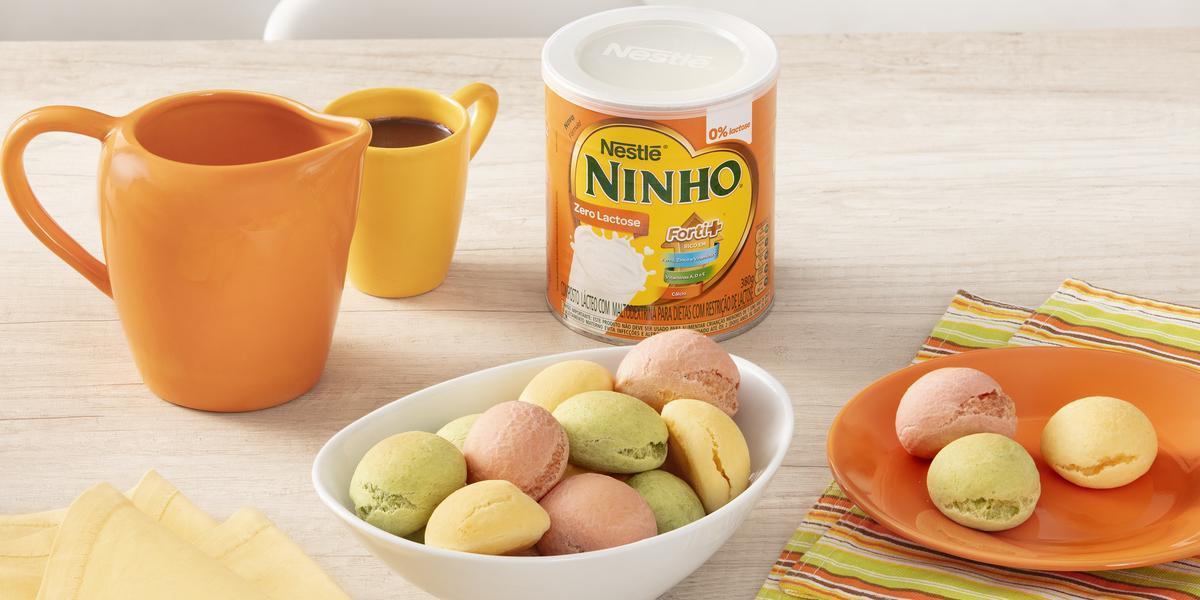 Fotografia em tons de branco e laranja de uma bancada branca com um recipiente branco oval, sobre ele pães de queijo. Ao lado um paninho listrado com um prato laranja com pães de queijo, uma lata de NINHO zero lactose, uma xícara e uma jarra laranjas.