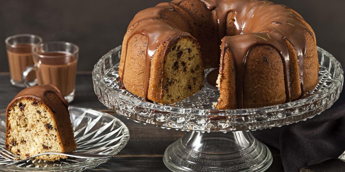 Fotografia em tons de marrom e preto de uma bancada preta vista de frente. Contém um prato redondo transparente com uma fatia de bolo com calda de chocolate por cima, um recipiente transparente para servir o bolo com o bolo sem uma fatia e calda por cima.