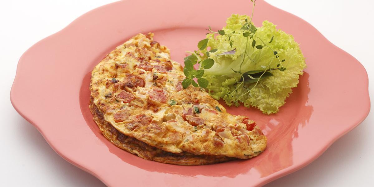 Foto de um prato rosa com um omelete em cima e algumas folhas de alface decorando