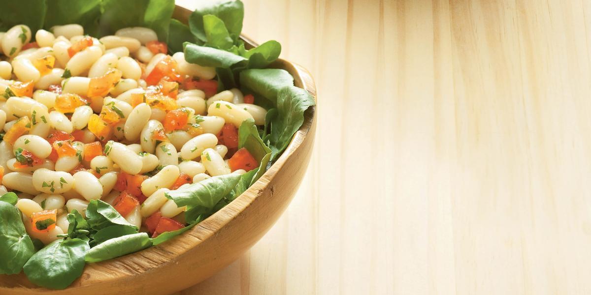 Fotografia de uma mesa de madeira com um bowl de madeira em cima com a salada dentro com folhas, feijão e cenoura.