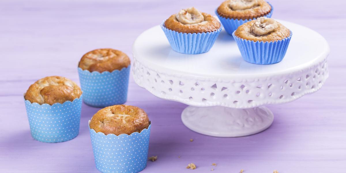 Foto de 6 cupcakes em forminhas azuis. 3 destes estão em uma mesinha branca e 3 estão ao lado da mesinha