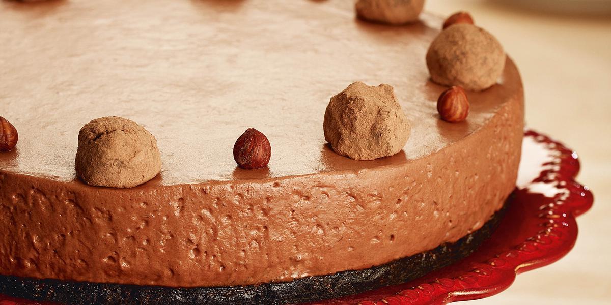 Fotografia em tons de chocolate, grafite e vermelho, tendo ao centro torta de chocolate sobre boleira vermelha e guardanapo grafite; ao fundo pratos empilhados com um talher por cima, tudo sobre bancada de madeira.