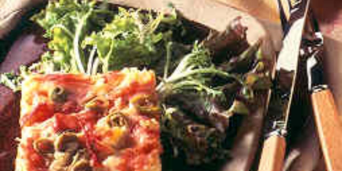 Fotografia em tons de verde em uma bancada de madeira com uma toalha bege colorida, um prato quadrado roxo com o pedaço da torta com azeitonas e ovos e ao lado salada de folhas verdes.