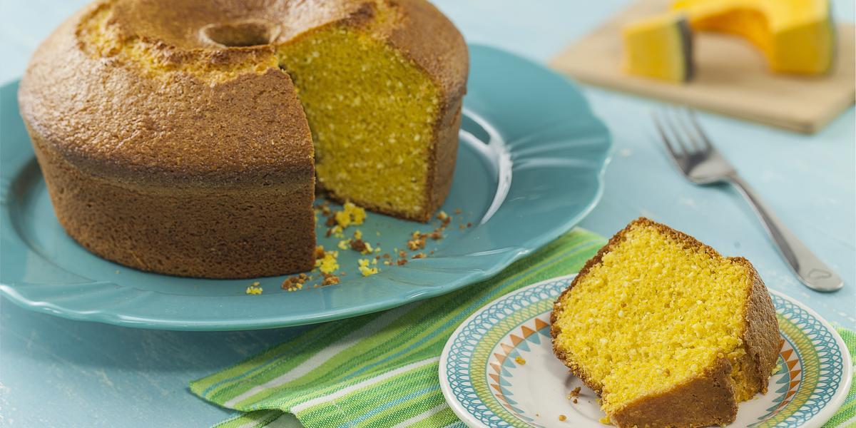 Fotografia em tons de azul de uma bancada azul com um prato azul, sobre ele um bolo de abóbora. Ao lado um paninho verde listrado com um prato redondo pequeno com uma fatia do bolo. Ao fundo uma tábua com uma fatia de abóbora.