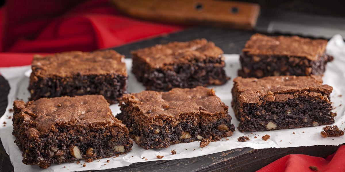 Foto de 6 pedaços iguais de brownie em cima de uma toalha branca e com uma faca de serra ao fundo da foto