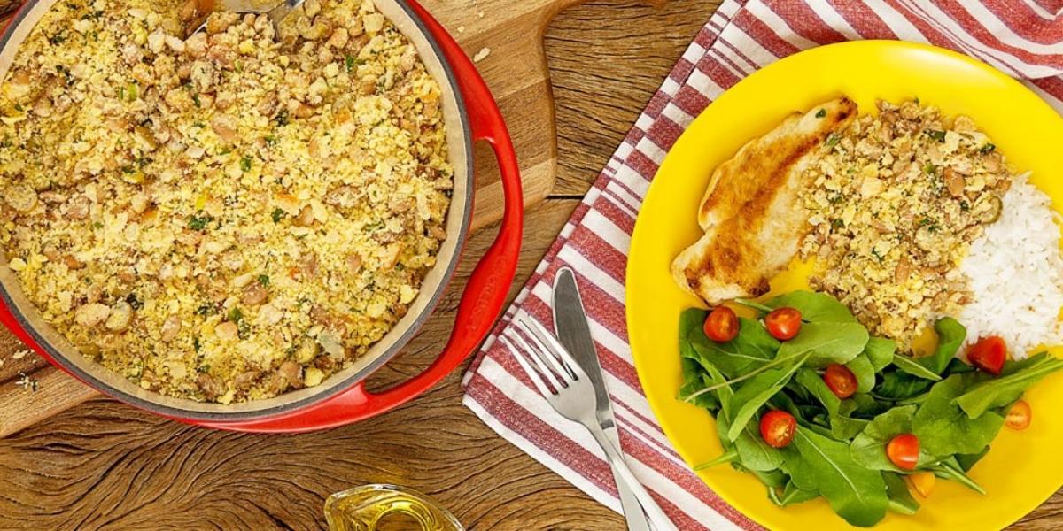 Fotografia em tons de amarelo e vermelho em uma bancada de madeira com um pano vermelho listrado com um prato amarelo com salada verde, arroz, frango e farofa de feijão. Ao lado, uma frigideira vermelha com farofa dentro.