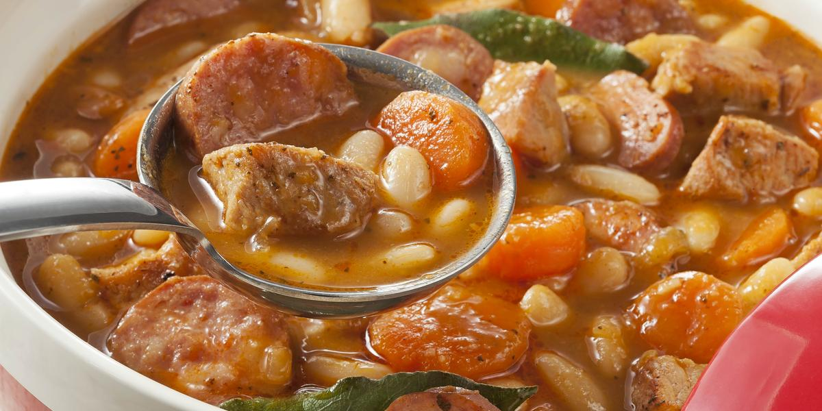 Fotografia em tons de laranja em uma mesa branca com um prato redondo fundo com o feijão branco cozido com linguiça e vegetais.
