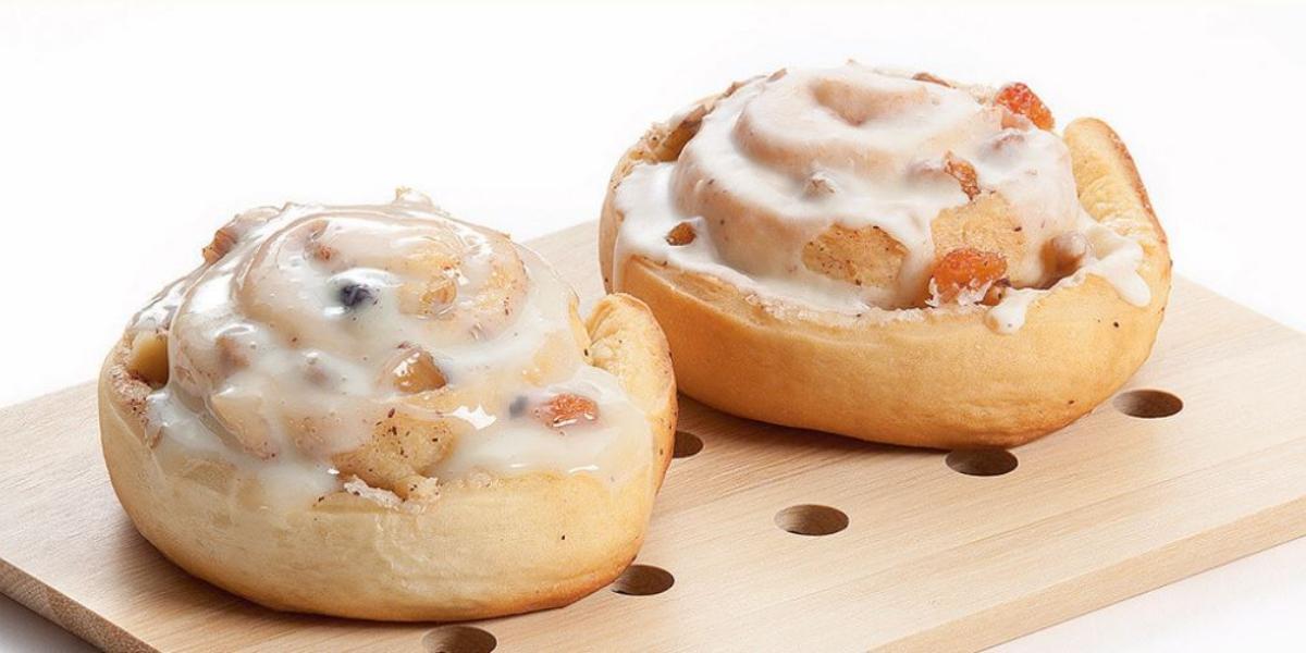 Fotografia em tons de pardo e branco vista de frente. Em uma tábua de madeira cor parda contém dois pães com creme por cima.
