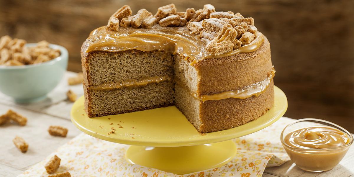 Fotografia em tons de amarelo em uma mesa de madeira com um pano bege com flores laranja e amarela, um suporte amarelo com o bolo de Moça Churros. Ao lado, um potinho com doce de leite. Ao fundo, um potinho azul com churros pequenos.