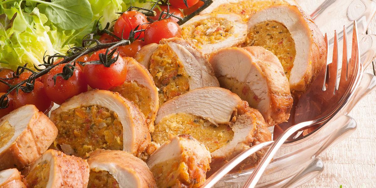 Fotografia em tons de verde e bege em uma mesa de madeira clara com um prato fundo de vidro com os filés de frango cortados ao meio recheados de farofa e salada de alface e tomate servindo como acompanhamento.