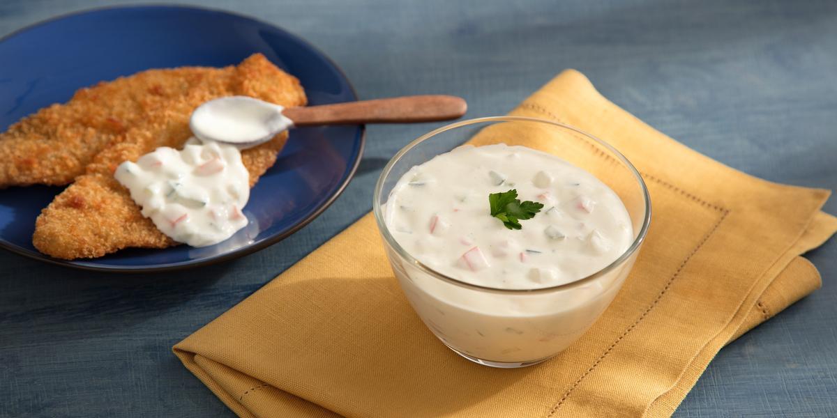 Fotografia em tons de azul, bege e branco com bancada azul contendo prato azul com porção de peixe empanado e molho com uma colher, ao lado potinho com um molho branco sobre guardanapo bege.