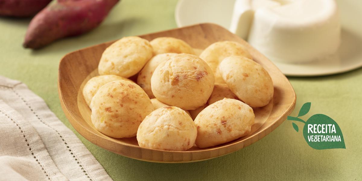 Fotografia em tons de verde e branco de uma bancada de verde clara com um recipiente de madeira clara com pães de queijo. Ao fundo um prato branco com o queijo minas e duas batatas-doces. Na frente um paninho branco.