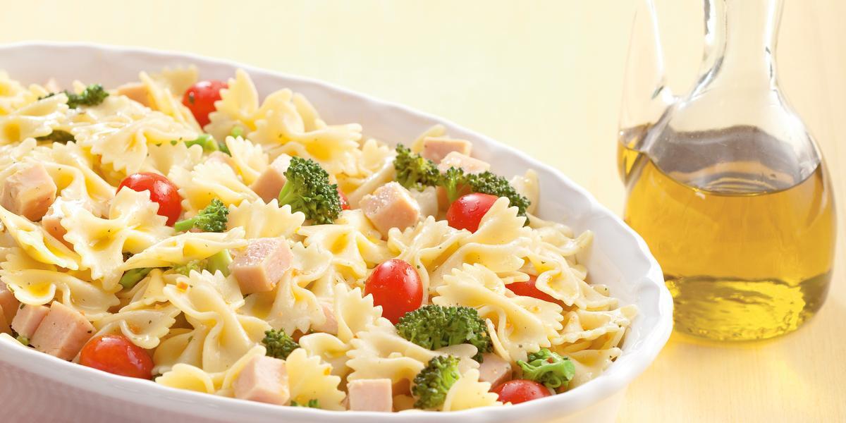 Fotografia em tons de amarelo em uma mesa de madeira com um pano quadriculado em vermelho, um recipiente oval branco com a salada de macarrão. Ao lado, um potinho com azeite.