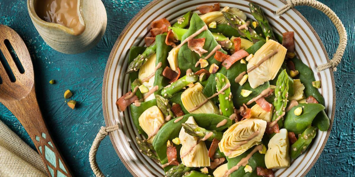 Incorpora el aderezo a la ensalada y mezcla bien cubriendo todos los vegetales. decora con los pistachos picados y sirve enseguida.