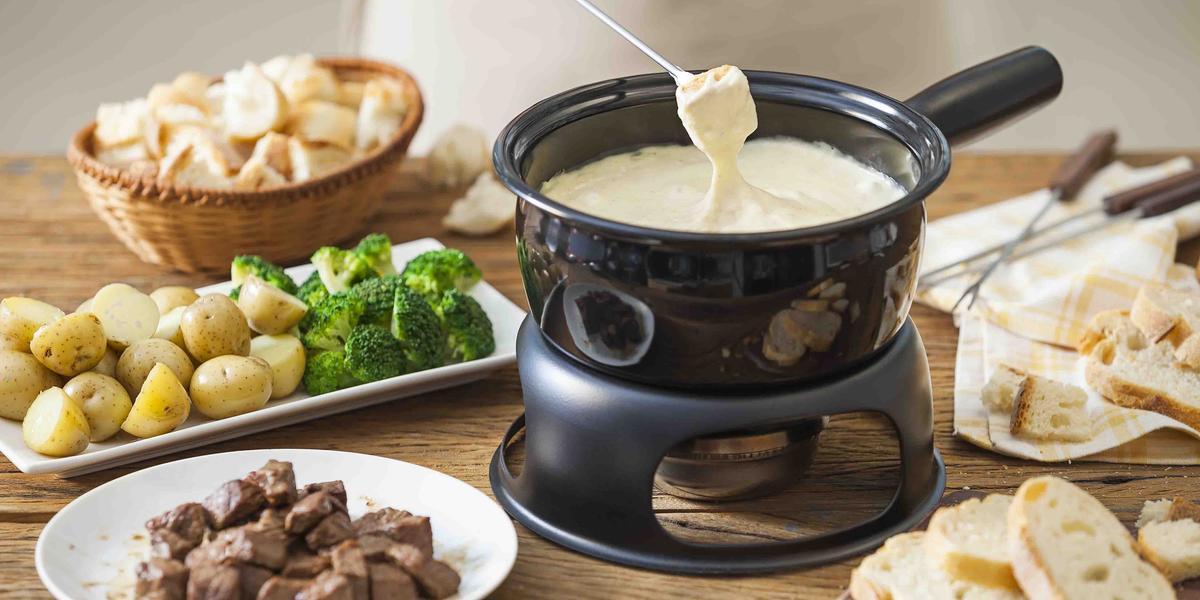 Fotografia em tons de marrom e beje de uma bancada de madeira com uma panela de fondue preta com fondue de queijo. Ao lado um prato redondo com carne, um prato retangular com batatas e brócolis, e uma cesta com pães.