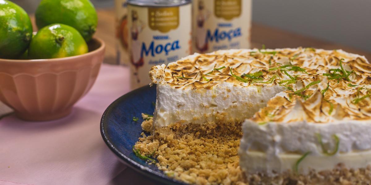 Foto de uma bancada, sobre ela há uma prato azul com a receita da Torta de Limão Fácil sem uma fatia, um pote rosa com limões verdes e algumas latas de Leite Moça ao fundo