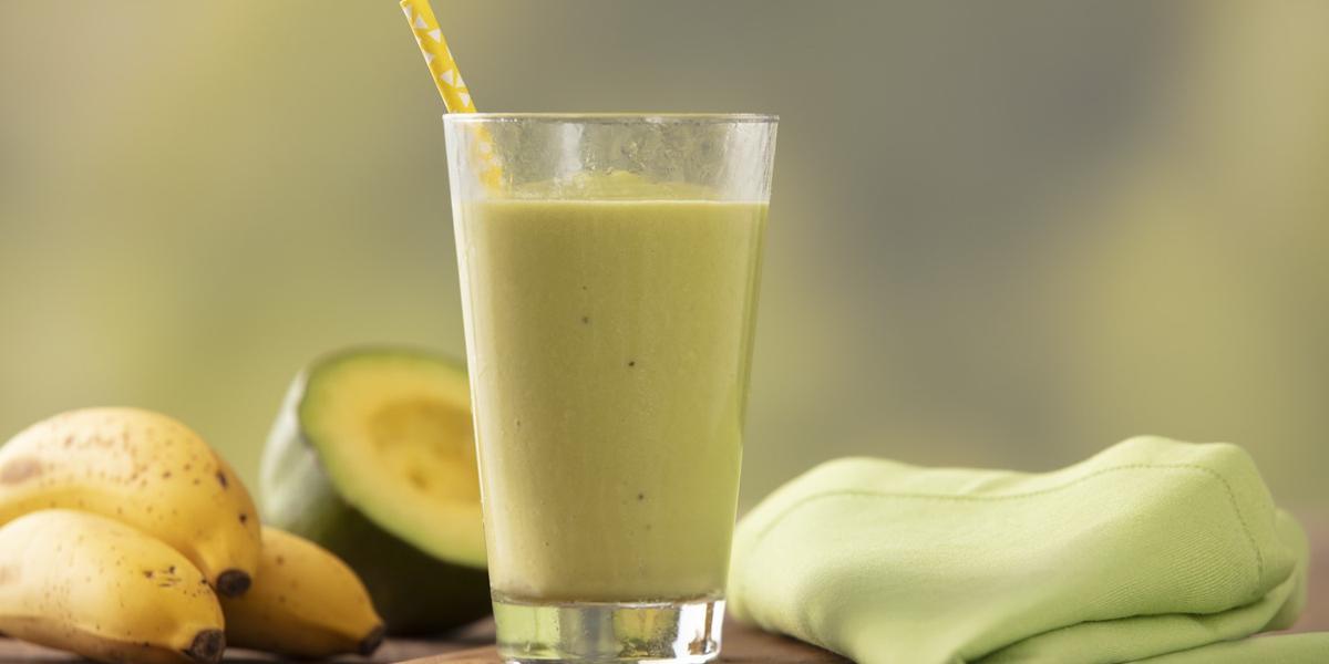 Fotografia em tons de verde e amarelo de uma bancada de madeira com um paninho verde e um apoio de copo de madeira, sobre ele um copo de vidro com a vitamina de abacate e um canudo amarelo. Ao fundo três bananas e meio abacate.
