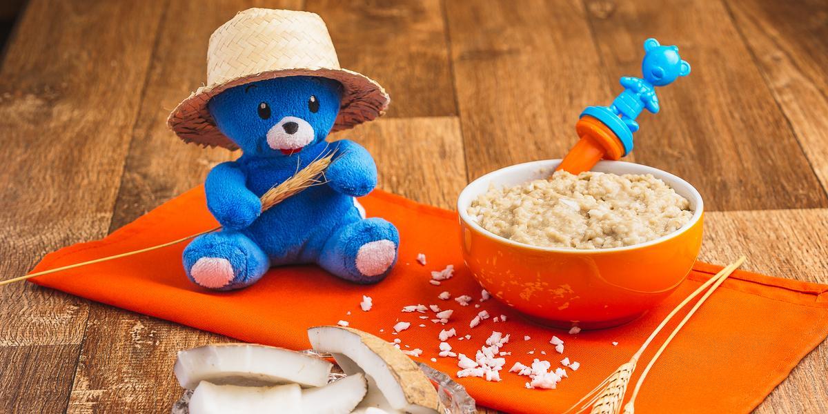 Fotografia em tons de laranja e azul de uma bancada de madeira com um paninho laranja e um pote laranja com a papinha. Na frente, fatias de coco seco decorando e uma pelúcia azul com chapéu de palha.
