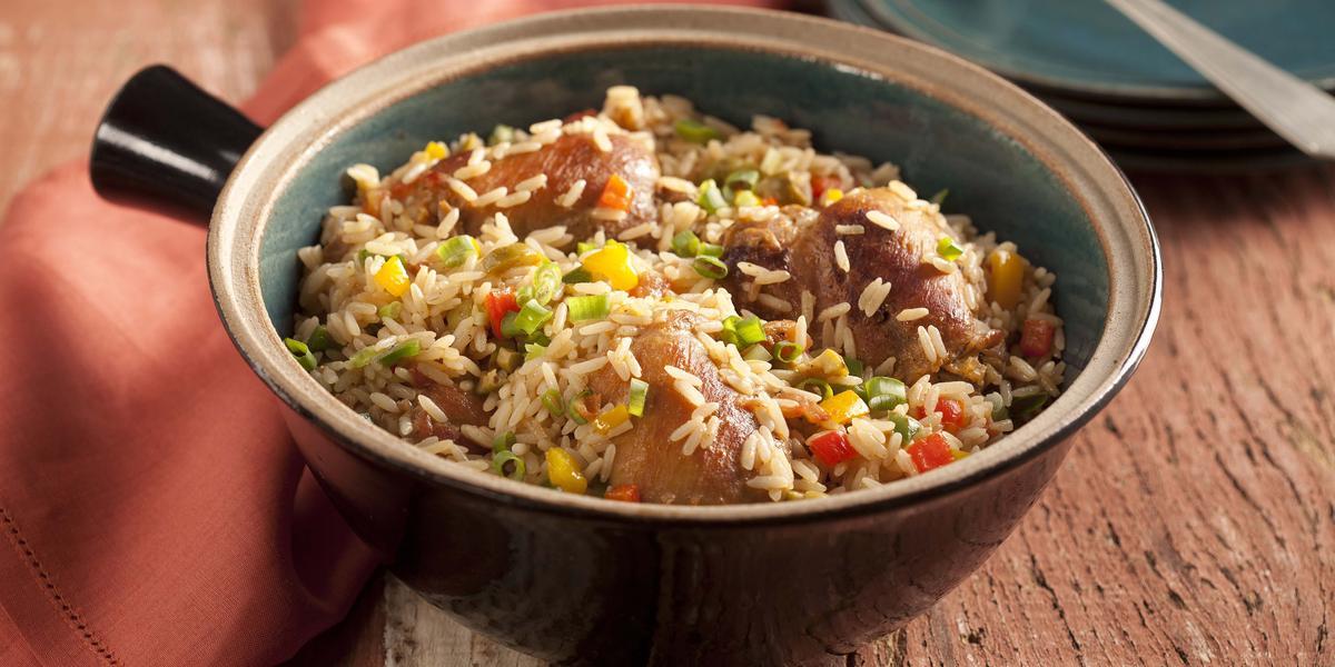 Fotografia em tons de marrom, contém um recipiente redondo com arroz e pedaços de frango