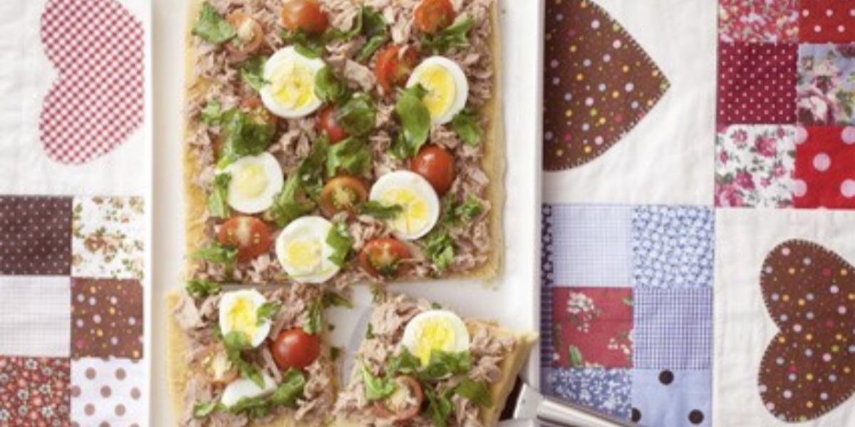 Fotografia em tons de branco, azul e vermelho de um paninho estampado com um prato retangular branco, sobre ele uma focaccia.