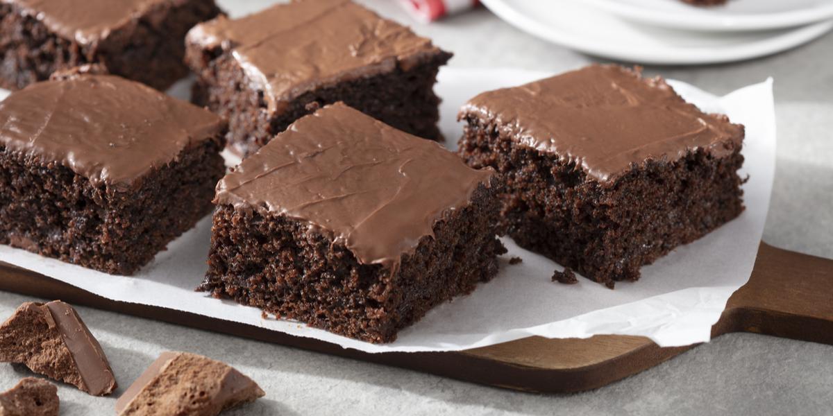 Fotografia em tons de marrom e branco de uma bancada branca  com uma tábua de madeira, sobre ela um papel manteiga com pedaços de bolo de chocolate zero. Ao fundo dois pratos brancos com uma fatia de bolo de chocolate e um paninho vermelho e branco.